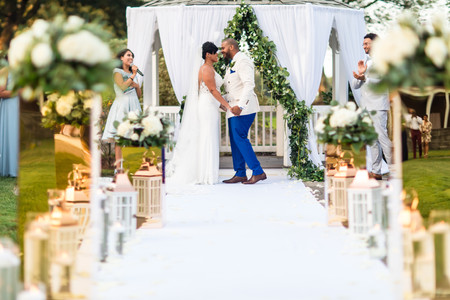 Wide shot angle of the groom leaning in to kiss his now wife as the bilingual wedding officiant from Once Upon A Vow pronounces them officially married