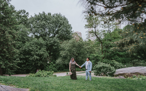 Wide-shot portrait of newly married couple holding hands looking at one another in the Central Park fields with buildings peaking behind the trees, post-ceremony led by Spanish-speaking officiant from Once Upon A Vow