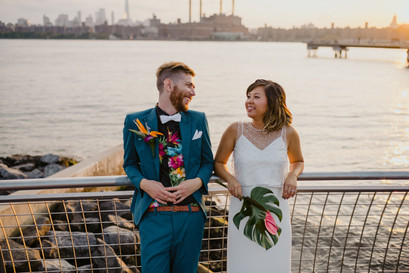 Newlywedded couple leans back on a metal guard rail overlooking the water while they smile at each other in Greenpoint, Brooklyn's Transmitter Park