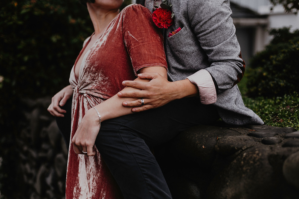 A close-up shot of a couple in a butch-femme relationship; one is wearing a pink velvet dress and being held by their partner who is wearing black pants and a grey blazer, the queer officiant from Once Upon A Vow