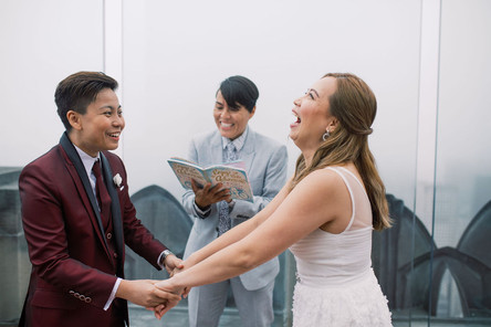 Butch/femme Asian couple holding hands and laughing at something queer officiant from Once Upon A Vow read from their ceremony; masculine presenting bride is smiling and appears to be in agreement and femme bride is cracking up with her had tilted back from laughing.