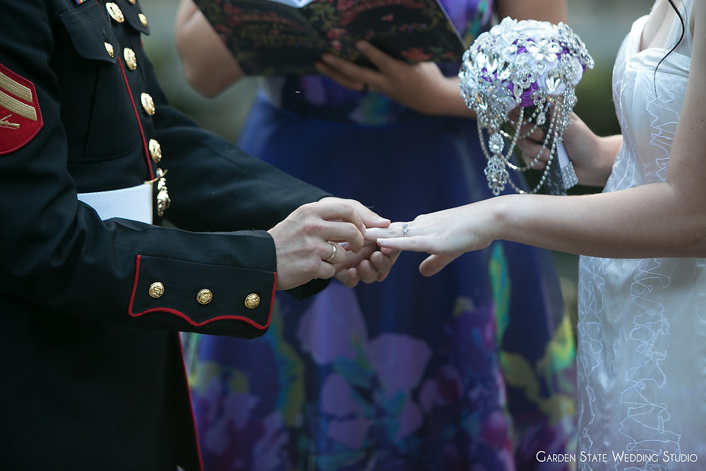 Marine putting a wedding ring on his beautiful bride during the wedding ceremony as she holds a bejeweled bouquet and wedding officiant of Once Upon A Vow dressed in purple conducts modern ceremony