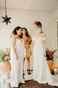Photo of intimate ceremony officiated by feminist wedding officiant from Once Upon A Vow marrying two laughing and smiling brides, one wearing a v-neck one piece romper with floral shoulder and the other wearing an off the shoulder white wedding dress with floral crown