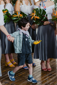 Photo of ring bearer holding his mom's hand and a pineapple platter with ring pops that he's bringing to the couple during the fun ceremony officiated by Once Upon A Vow in Brooklyn's Greenpoint Loft