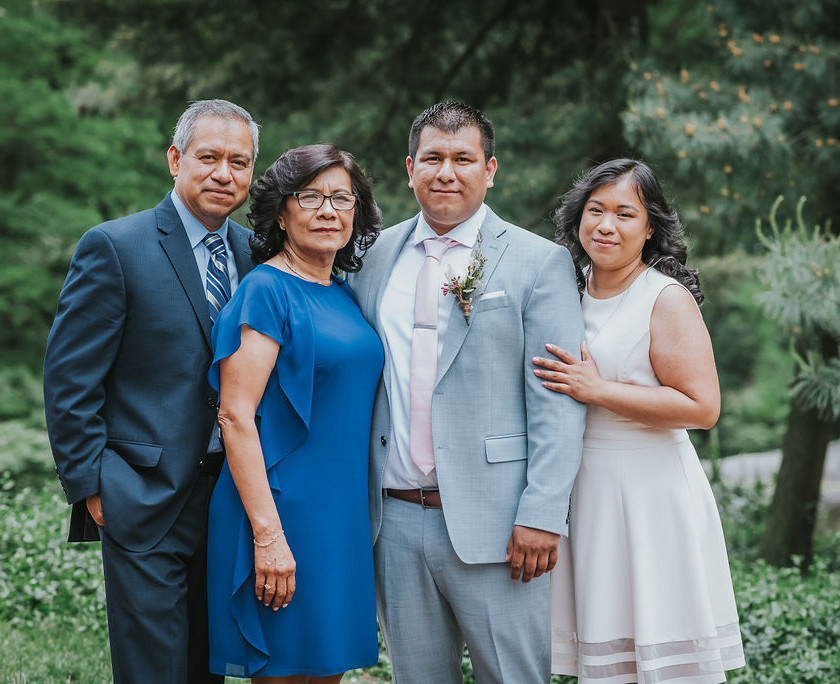 Family portrait between the groom, his parents, and sister in Central Park before the elopement ceremony begins by Spanish-speaking officiant from Once Upon A Vow