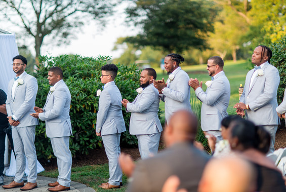 Groomsmen in light grey suits clapping and all looking towards the couple and officiant during the bilingual wedding ceremony officiated by Once Upon A Vow at Pelham Bay Golf Course