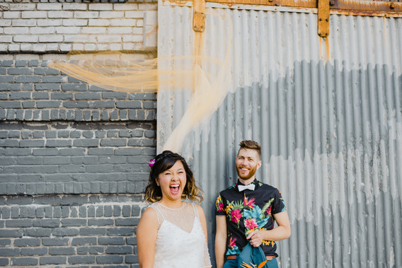 Playful photo from the bust up of newly married couple, bride laughing as her ombre yellow veil floats above her head and husband is smiling in the background, holding his teal blazer with a grey brick and metal background in Greenpoint, Brooklyn
