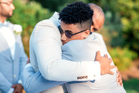 Groom and son embrace each other in a deep hug right before the bilingual ceremony officiated by Once Upon A Vow begins