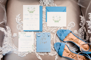Periwinkle blue invitation flat lay with blue Sam Edelman heels and wedding rings laid across the bride's veil