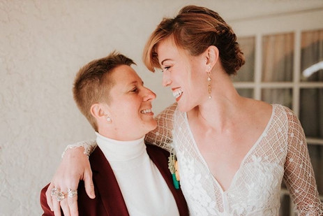 Close up photo of an LGBTQ couple looking at each other, holding each other close, and smiling; one in a  maroon suit with cream turtleneck and the other with a beaded v-neck white wedding dress.