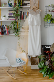 White wedding dress with beaded overlay hanging on wooden hanger surrounded by books on bookshelf and plants in a Greenpoint Loft home