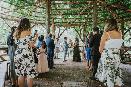Wide photo of elopement ceremony in Central Park's Cop Cot with the couple and Spanish-speaking wedding officiant from Once Upon A Vow at the center and the guests surrounding them