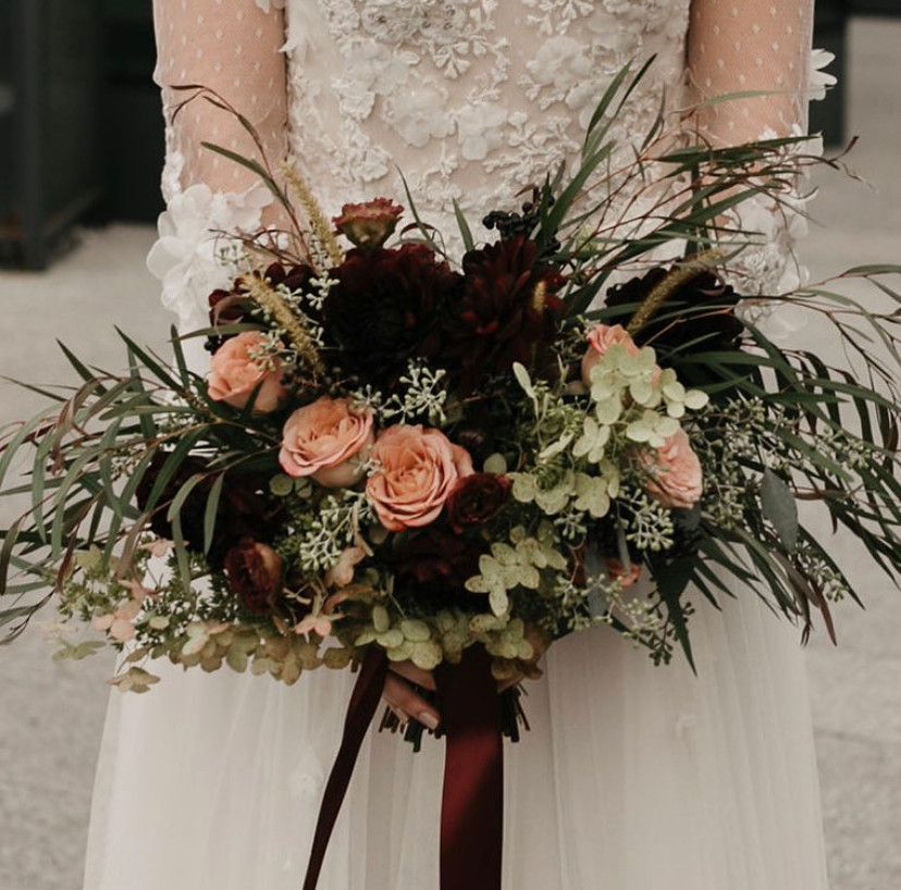 Deep toned bride's bouquet and crimson red ribbon designed by Flying Little Birds being held by a bride dressed in white with sheer sleeves, floral arrangements to be delivered for zoom weddings in New York City