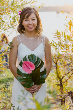 Bridal portrait of beautiful smiling asian bride holding her tropical bouquet, the beaded overlay in sharp focus set among natural greenery in Greenpoint Brooklyn