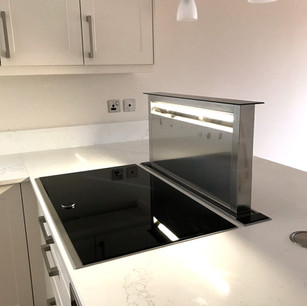 Modern white kitchen with extractor integrated into worktop