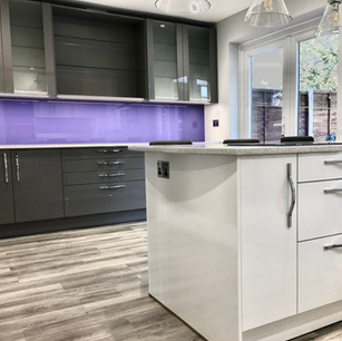 Modern white kitchen with purple backsplash