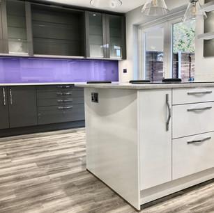 Modern white kitchen with purple backsplash