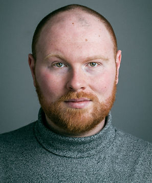 A portrait of Mercury - a bald man with hazel eyes and a ginger beard - wearing a grey sweater