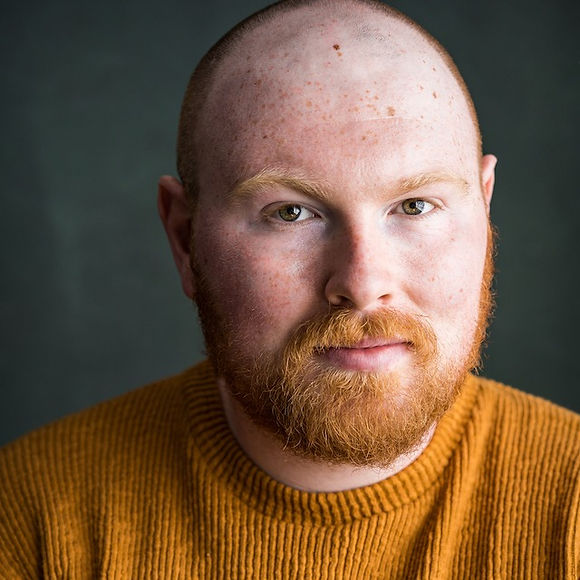 A portrait of a queer, bald, hazel-eyed man with a ginger beard wearing a burnt orange sweater.