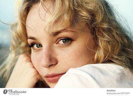 Junge blonde Frau, die über die Schulter schaut.