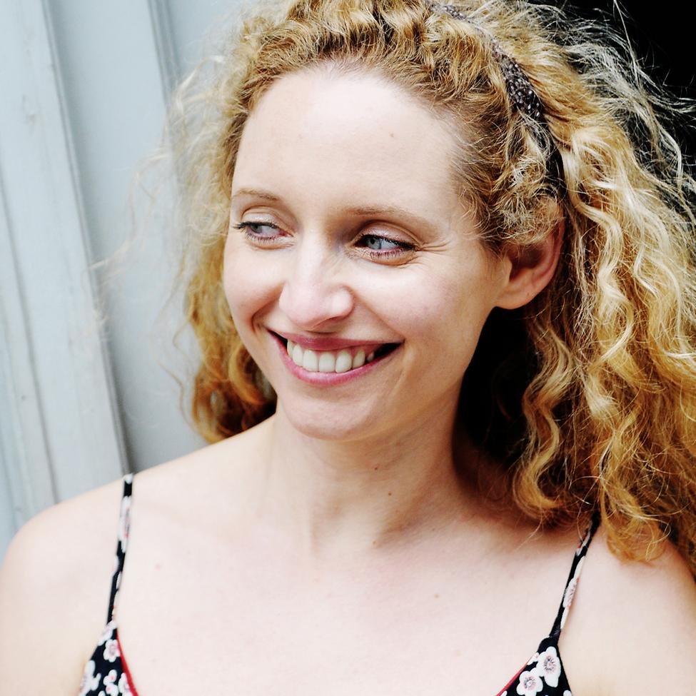 Sara Sommerfeldt lachend mit offenen blonden lockigen Haaren