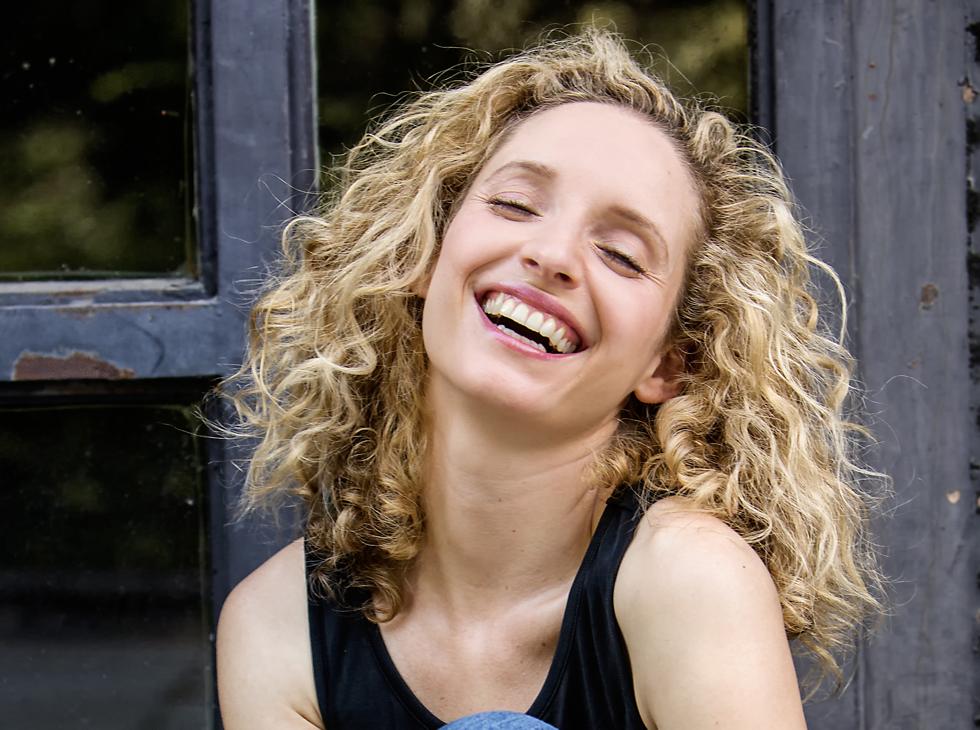 Sara Sommerfeldt lachend mit offenen Haaren.