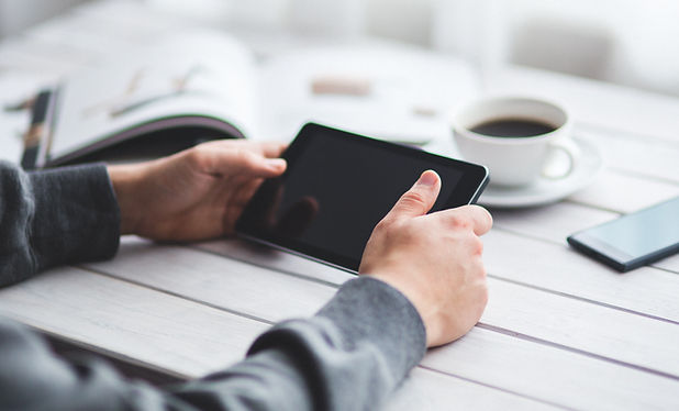 Hands holding a small tablet horizontally at a table with a book, coffee, and phone