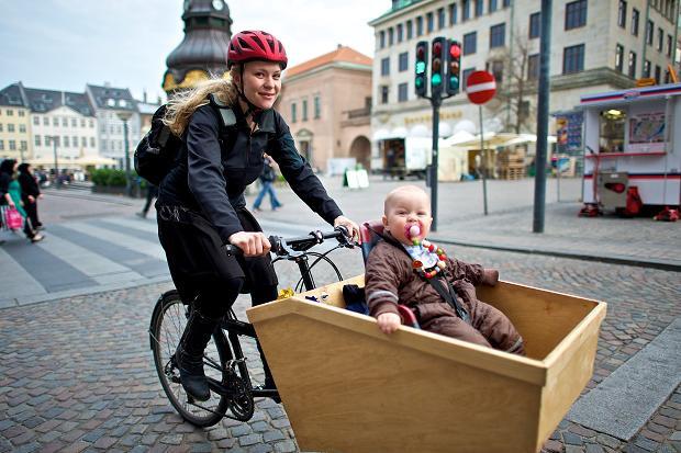 Uma mãe e seu bebê pedalam em Copenhague