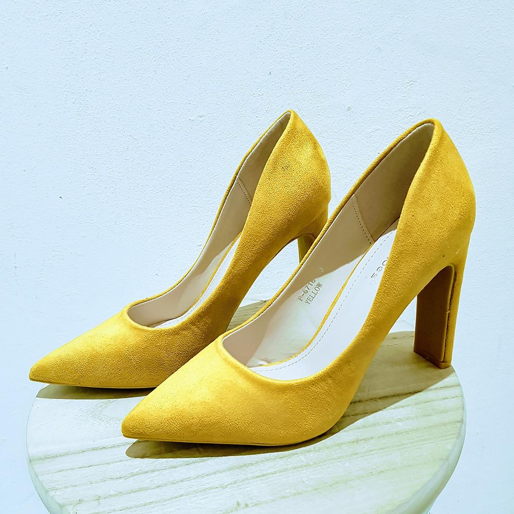 Gele pump met stevige en brede hak.