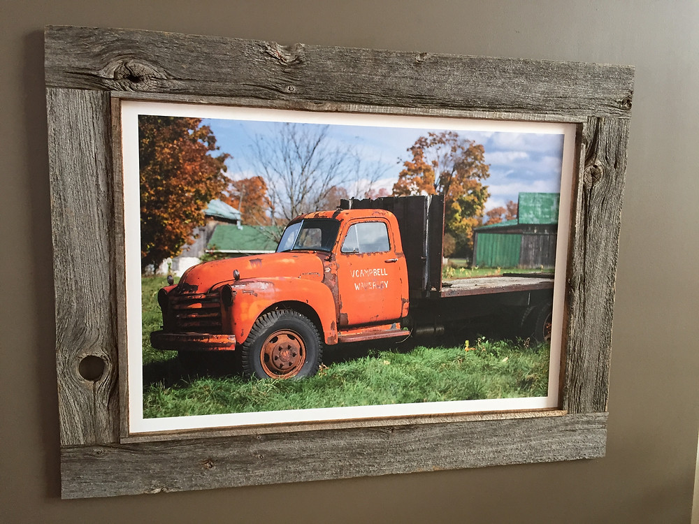 old truck surrounded in barn board frame
