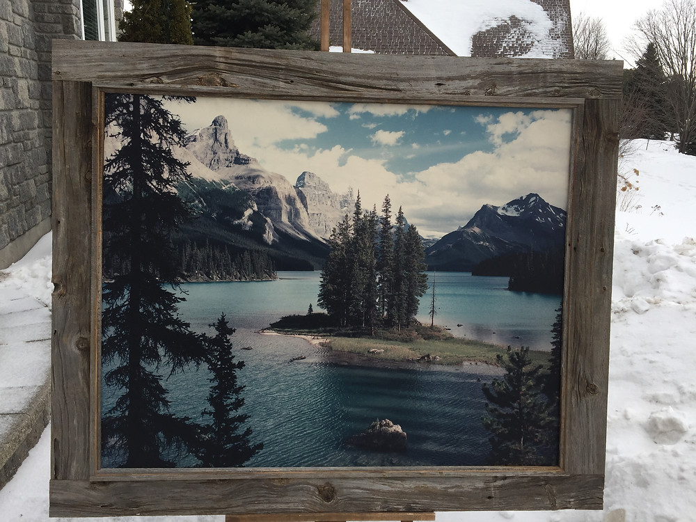 mountains and lake surrounded in barn board frame