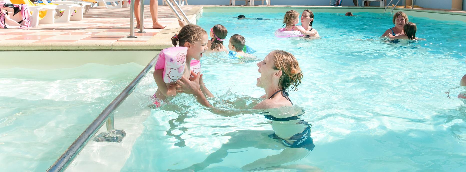 Femme et son enfant a la piscine d'un camping