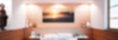 Image montrant l'interieur d'une chambre a coucher aux tons bois ou est accrochee une photo panoramique sur dibond d'Antoine Tatin representant la grande plage des Sables d'Olonne.