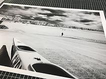 Photo d'un tirage en noir et blanc d'Antoine Tatin representant un canoe sur la plage des Sables d'Olonne et pose sur une table de travail.