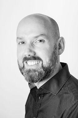 Portrait en noir et blanc d'Antoine Tatin souriant a l'objectif.
