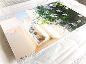 Tirage photo d'Antoine Tatin sur dibond pose sur une feuille de papier de soie avant emballage et livraison. La photo represente une ruelle fleurie de la Chaume, aux Sables d'Olonne.