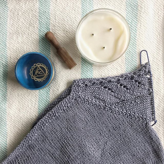 A knit sweater in progress, a candle, and a singing bowl