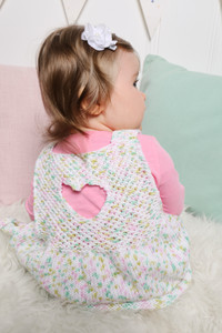 A baby modelling a pink, white and green knit pinafore displaying the back heart cutout detail