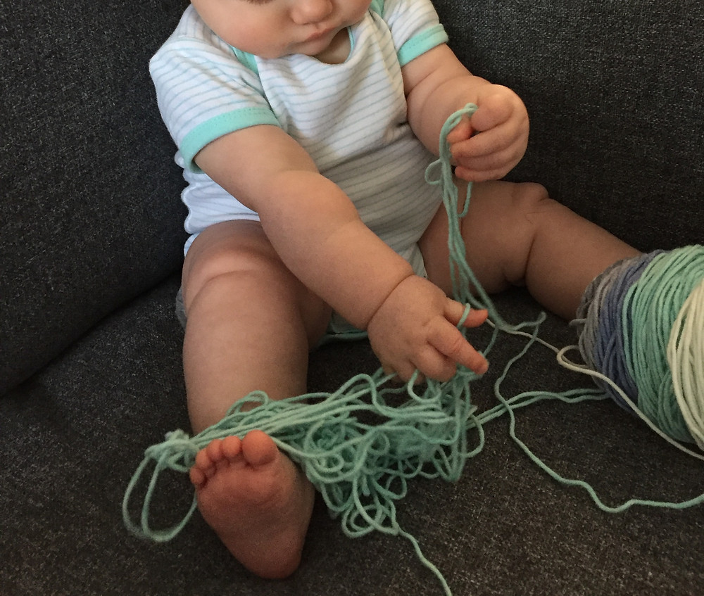 Pudgy baby fingers and toes, tangled in aqua cotton yarn