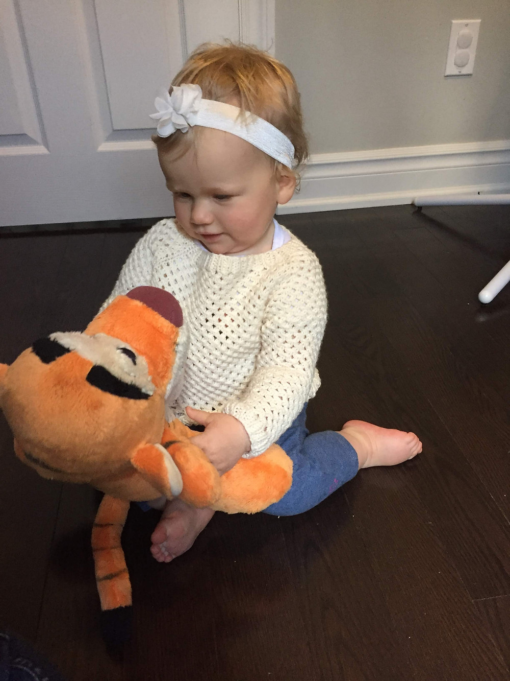 A blonde baby in a cream lace pullover, holding a Tigger doll