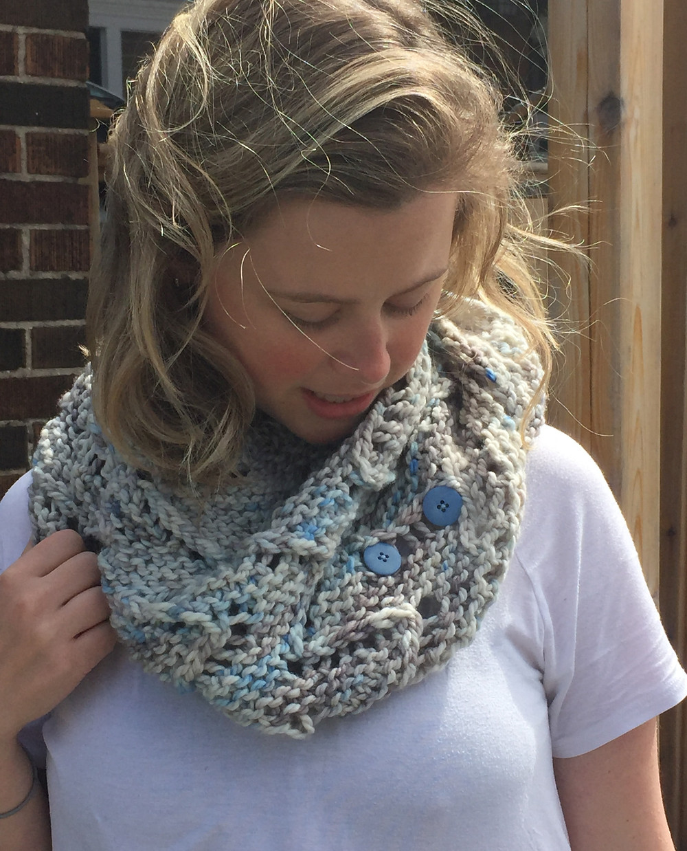 Nicky modelling Chasm, a blue and grey chunky lace shawlette fastened with two buttons around her neck like a cowl