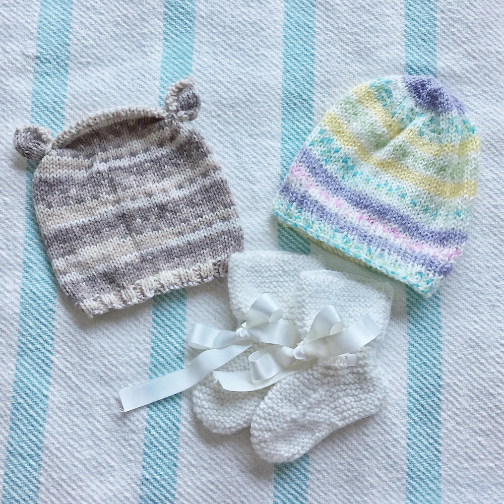 "A taupe striped baby hat with cinched ""ears"", a purple, white, pink, and blue striped baby toque, and white handknit baby booties"