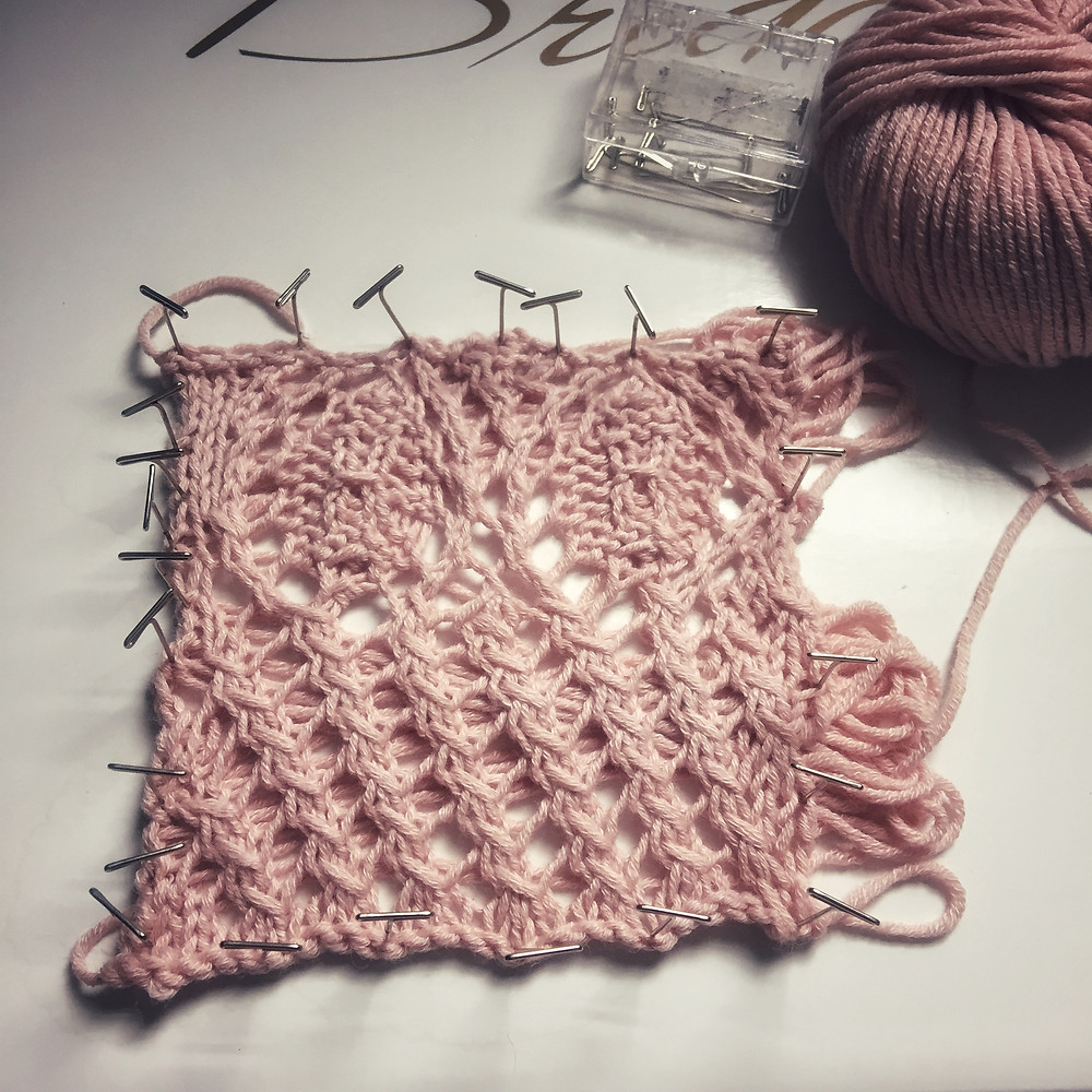 A pink lace swatch pinned out
