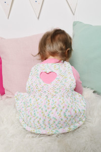 A baby modelling a pink, white and green knit pinafore displaying the back heart cutout