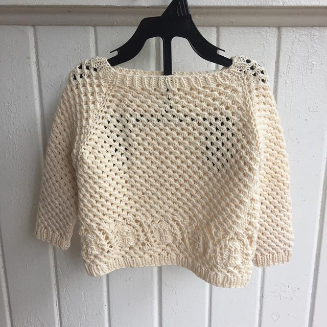 A cream baby raglan pullover in allover mesh with sand dollar lace motif across the hips, displayed on a hanger
