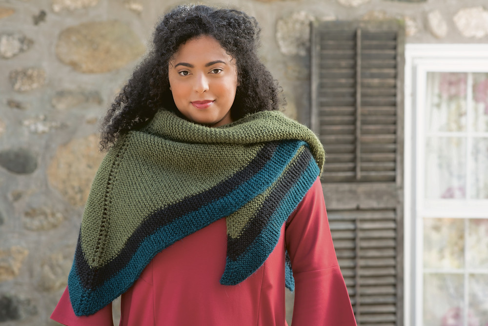 A woman with curly black hair models a green and black intarsia triangle shawl, inside a stone cottage.