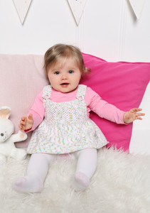 A baby modelling a pink, white and green knit pinafore