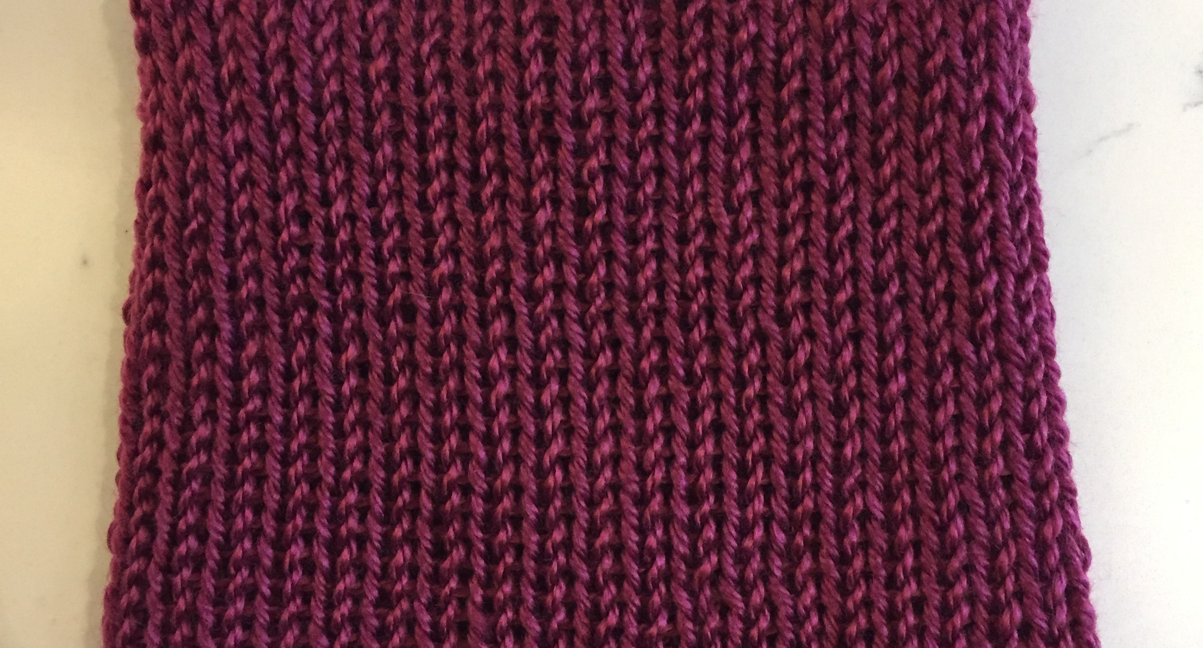 Burgundy kids knit hat with straight seam across the top