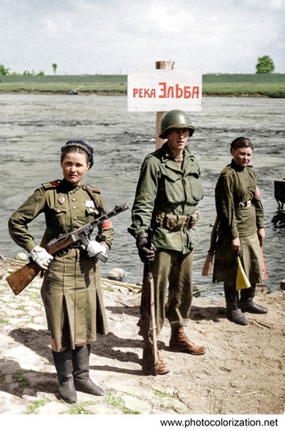 May 1945, Germany, An American soldier is flanked by two Red Army girls soldiers as they do guard duty on the River Elbe at Torgau, where the Allies met from the east and west.
