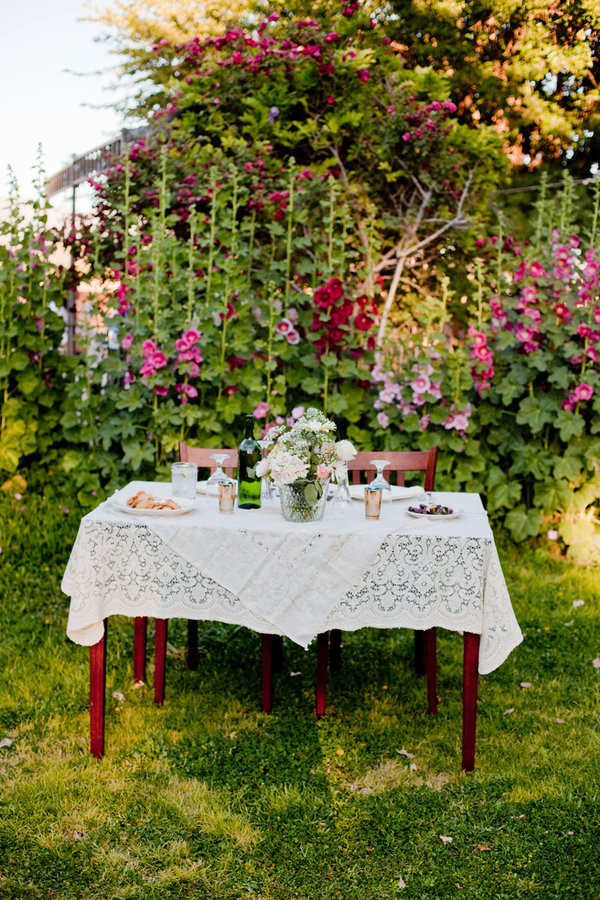 Sweetheart table with towering hollyhocks behind.